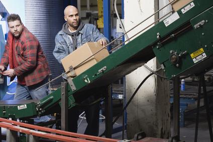 Two men operating conveyor belt